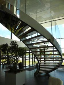 Escalier-cintré-limon-à-la-française-en-inox-poli-marches-en-chêne-garde-corps-en-verre-cintré-2-225x300