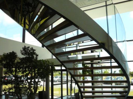 Escalier-cintré-limon-à-la-française-en-inox-poli-marches-en-chêne-garde-corps-en-verre-cintré-2-510x382