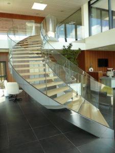 Escalier-cintré-limon-à-la-française-en-inox-poli-marches-en-chêne-garde-corps-en-verre-cintré-225x300