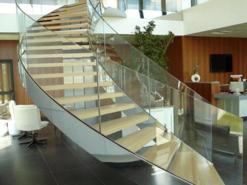 Escalier-cintré-limon-à-la-française-en-inox-poli-marches-en-chêne-garde-corps-en-verre-cintré-510x382