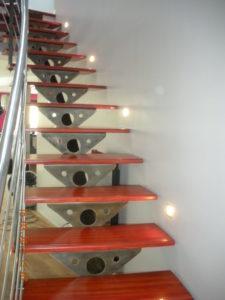 Escalier-limon-central-cintré-avec-support-de-marche-en-tôle-marches-en-padouk-avec-insert-inox-225x300