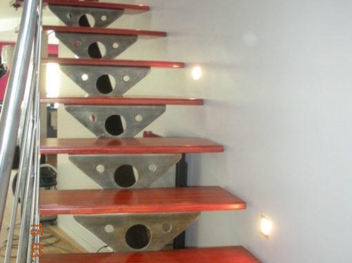 Escalier-limon-central-cintré-avec-support-de-marche-en-tôle-marches-en-padouk-avec-insert-inox-510x382